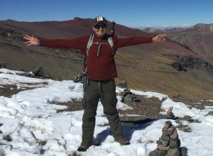 man standing in snow in front of peru mountain range