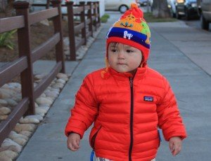 baby walking on side walk wearing patagonia red jacket