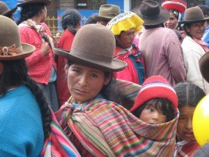 Andean woman lares valley community charity event with child