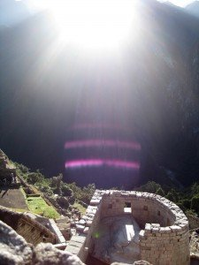 Sunrise on winter solstice in machu picchu, peru with sun illuminating the temple of the sun and altar within